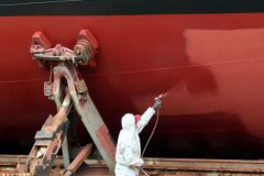 Applicator painting a boat hull