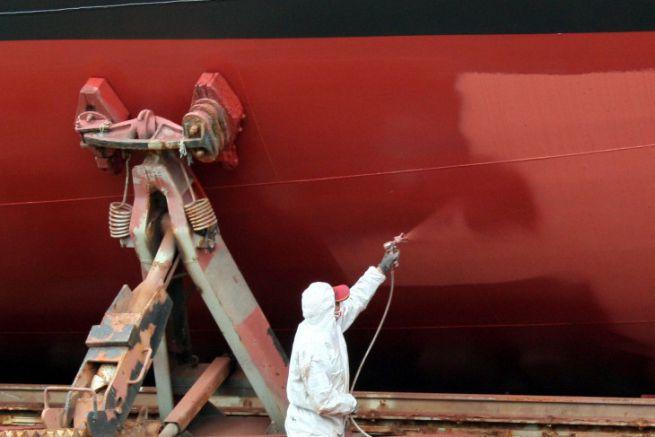 Applicator painting a boat hull